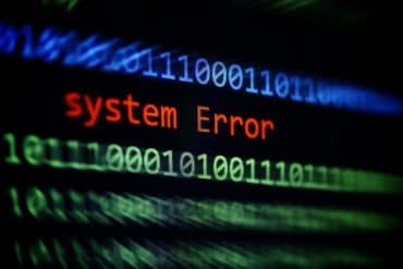 Binary code and error message on display showing risks of malware attack on Travelex