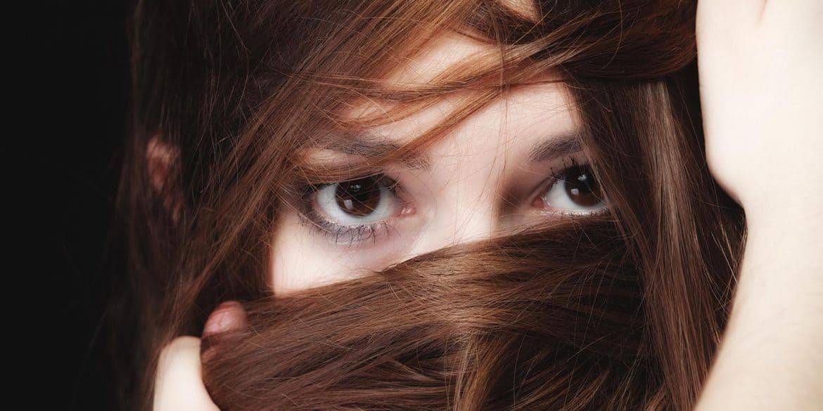Woman with face covered by hair showing how 2015 Ashley Madison data breach leads to new cyber extortion scams