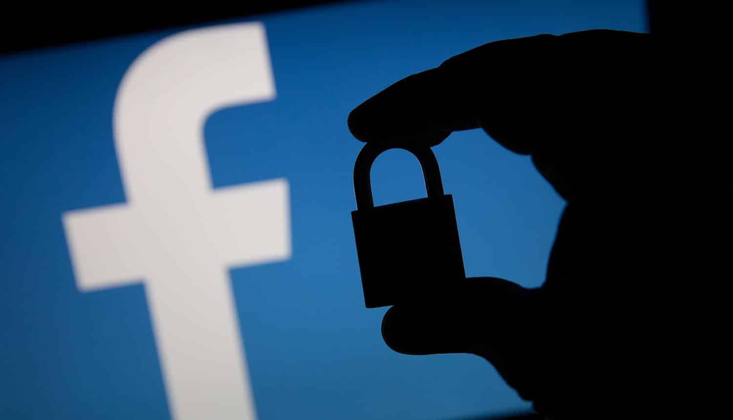 Silhouette of a hand holding a padlock in front of Facebook logo showing security flaw that led to biggest data breach