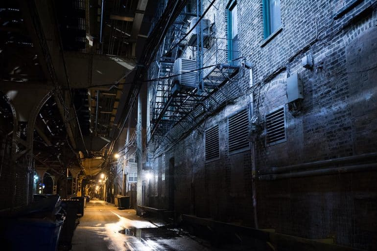 Dark urban alley at night showing the lurking risks of shadow IoT