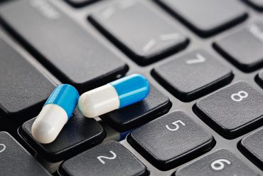 Two medical pills on keyboard showing the eight ways to keep patients' digital healthcare data safe