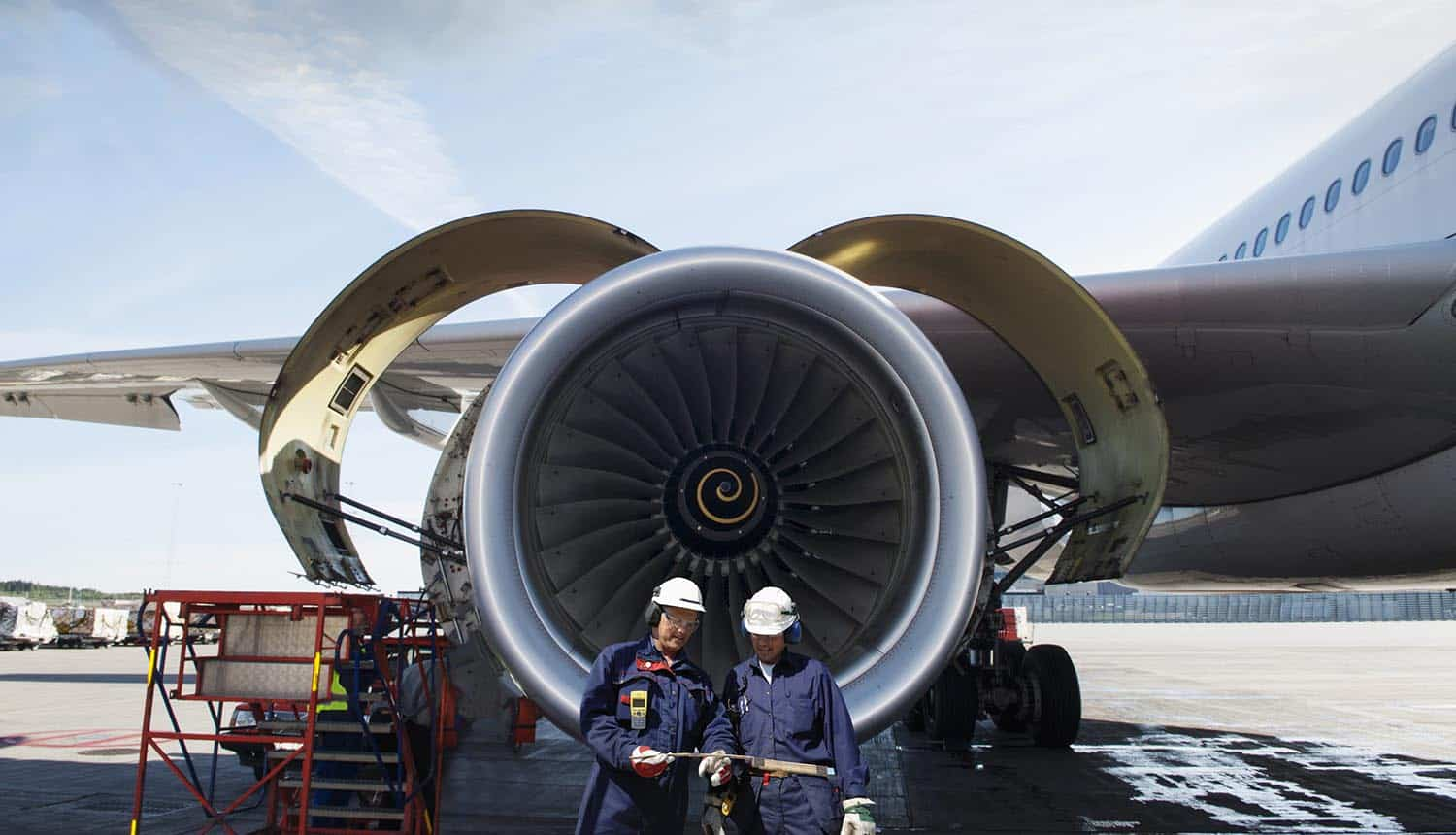 Mechanics standing in front of jet engine showing the importance of data security while airline industry is transforming to cloud-based technologies