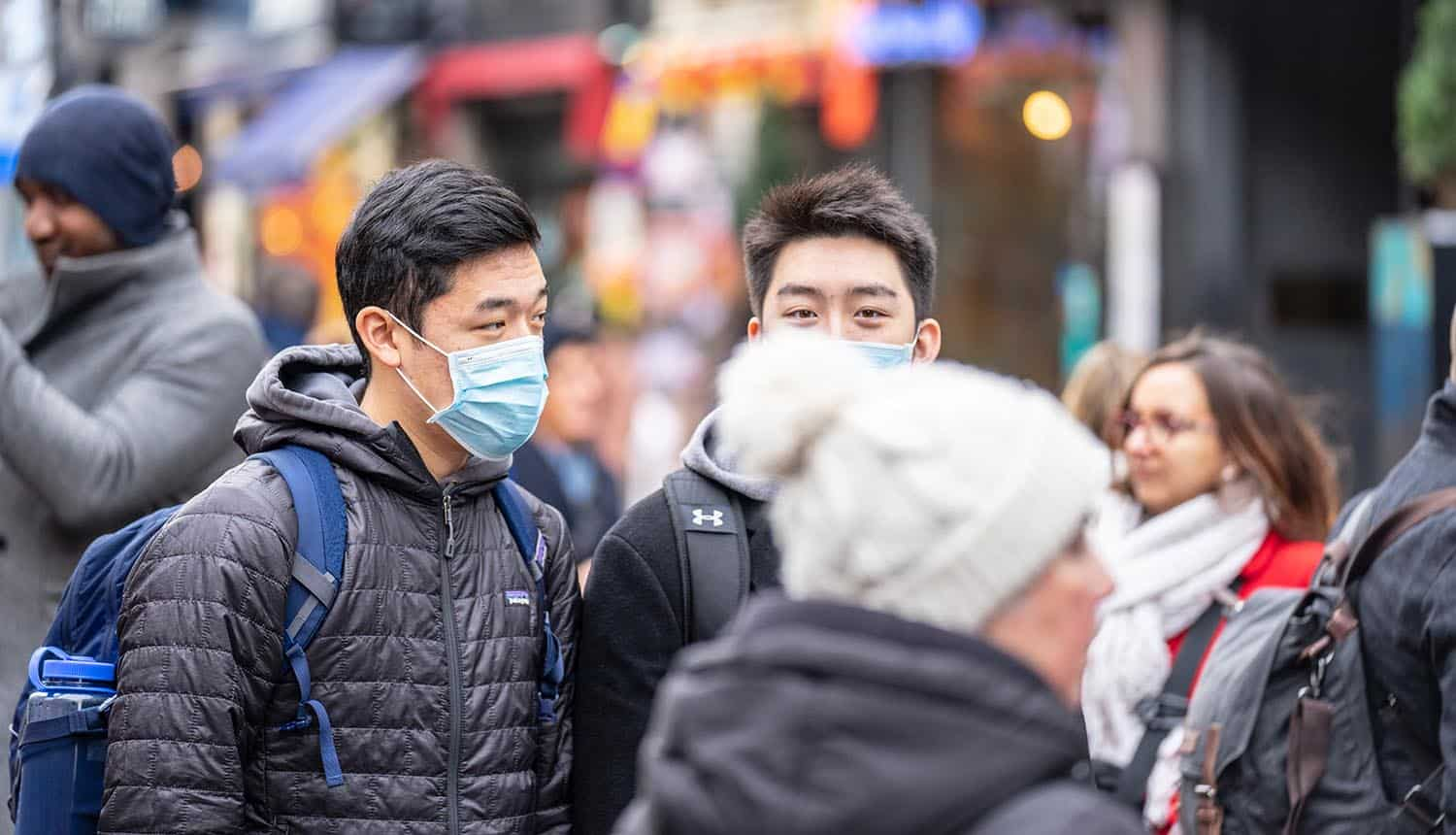 People wearing face masks on street showing the challenge to collect and handle health data under GDPR to combat coronavirus outbreak