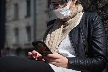 Woman in facial mask using mobile phone showing the DDoS attack on Federal health agency and ongoing disinformation campaign in U.S.