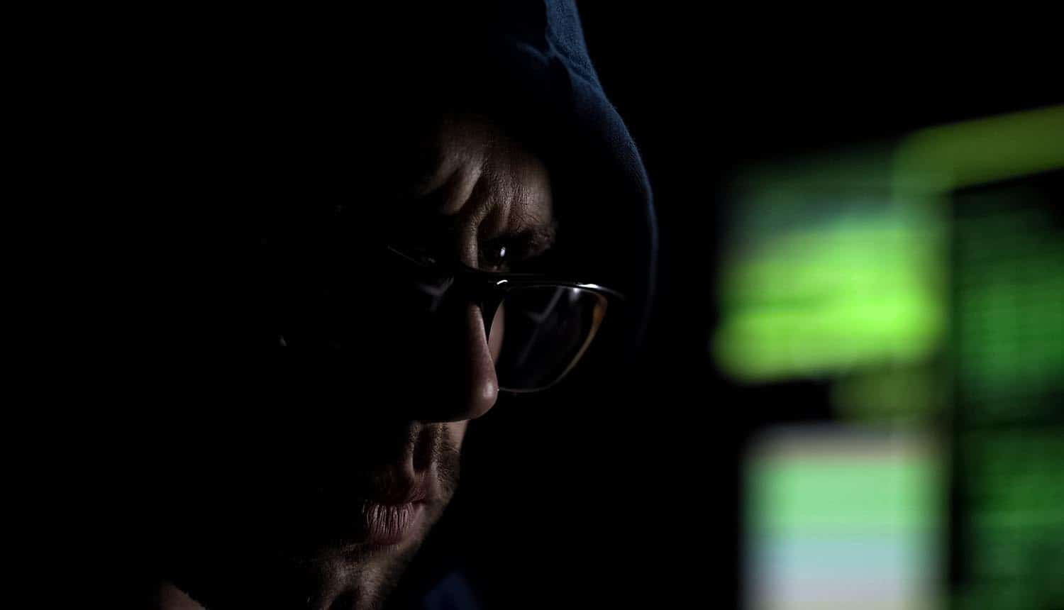 Hacker in glasses looking at screen showing cybercrime gangs promise to stop attacks on healthcare organizations during coronavirus crisis