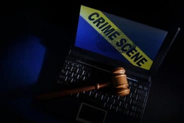 Legal gavel on a laptop with crime scene tape showing digital investigations being a major challenge for law enforcement