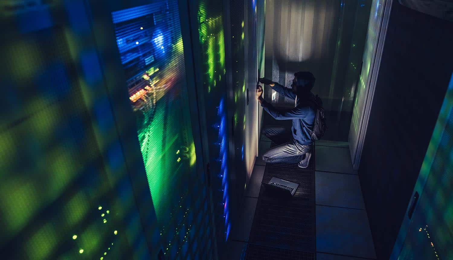 Hooded hacker working with laptop in dark data center showing the dangers of insider threats