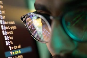 Part of face of young hacker in eyeglasses with reflection of screen with decoded information showing rise in malware-free attacks
