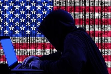 Hacker using laptop with U.S. flag in background showing the published report on the massive overhaul of U.S. cyber security policy