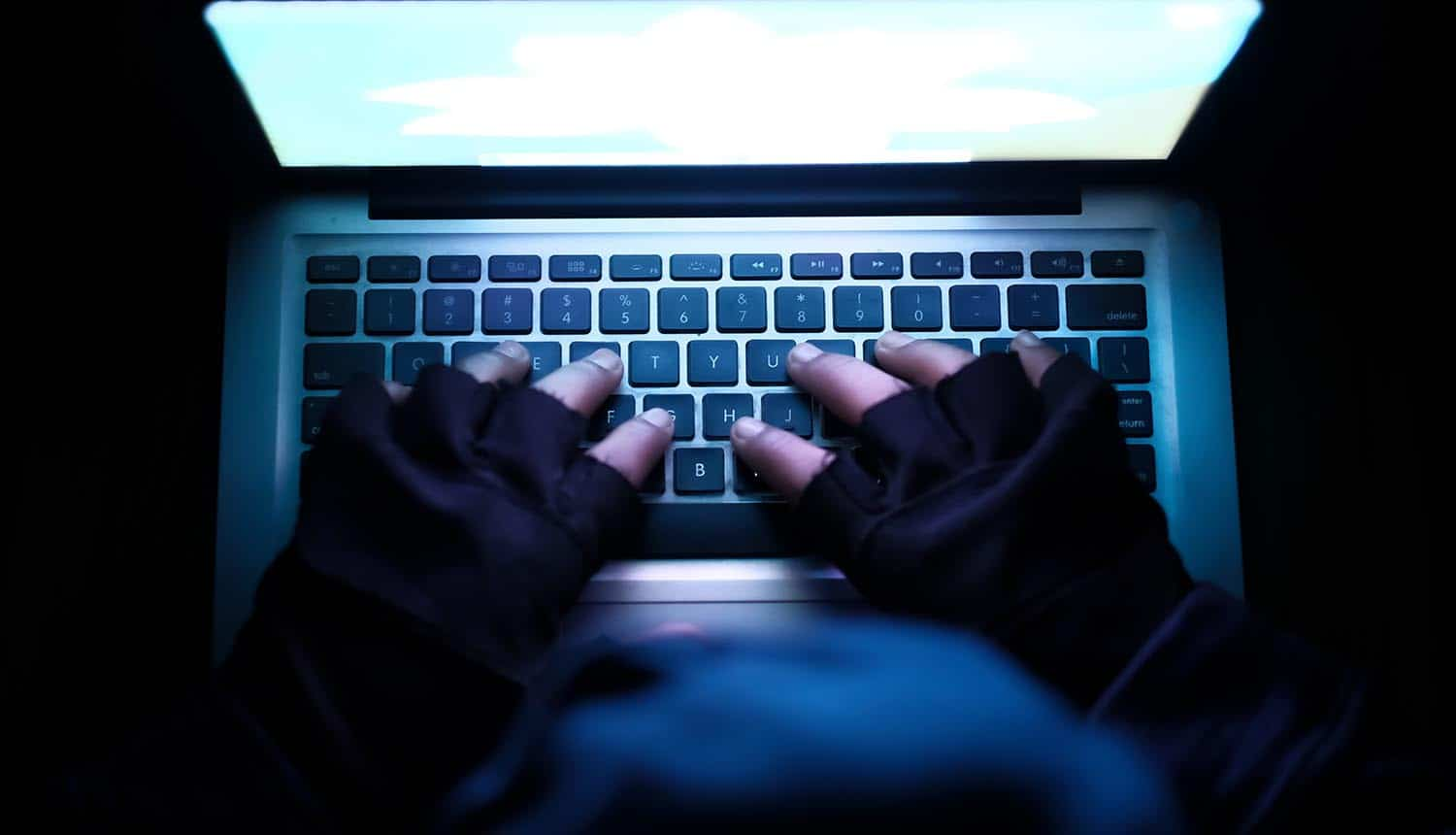 Hacker using laptop showing China's public accusation on CIA of 11 years of cyber espionage