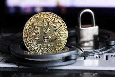 Gold bitcoin, handcuffs and a metal lock on a laptop showing the ransomware attack on FinTech company Finastra