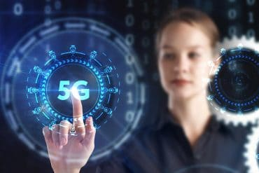 Woman touching 5G logo on virtual screen showing the importance of IoT security in 5G networks