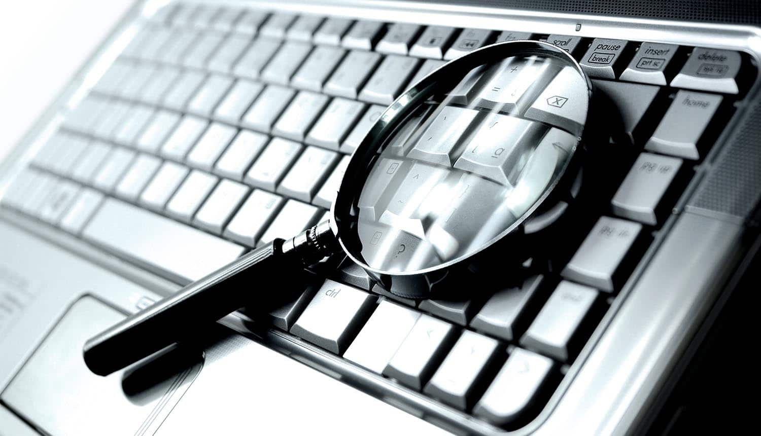 Magnifying glass on laptop keyboard showing the adversary attribution approach to fight cybercrime