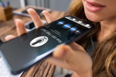Woman using voice assistant on mobile showing the vulnerabilities of voice assistants that are underlooked