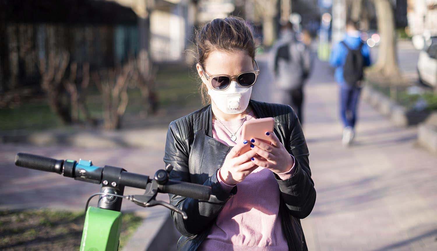 Woman on street in face mask using mobile showing the privacy and coverage concerns over the contact tracing app under development by Apple and Google