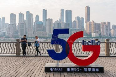 People using smartphone near a 5G sign showing introduction of 5G messaging service to unseat WeChat