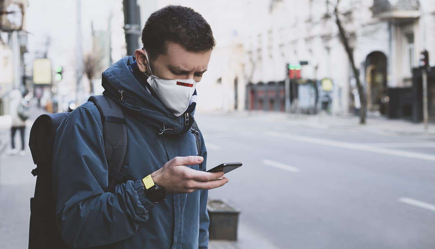 Man in mask using mobile on the street showing the attempt to balance public health measures with user privacy for contact tracing apps