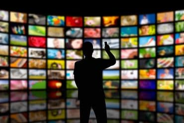 Man looking at multiple TV screens showing the cyber threats that rack the media and entertainment industry