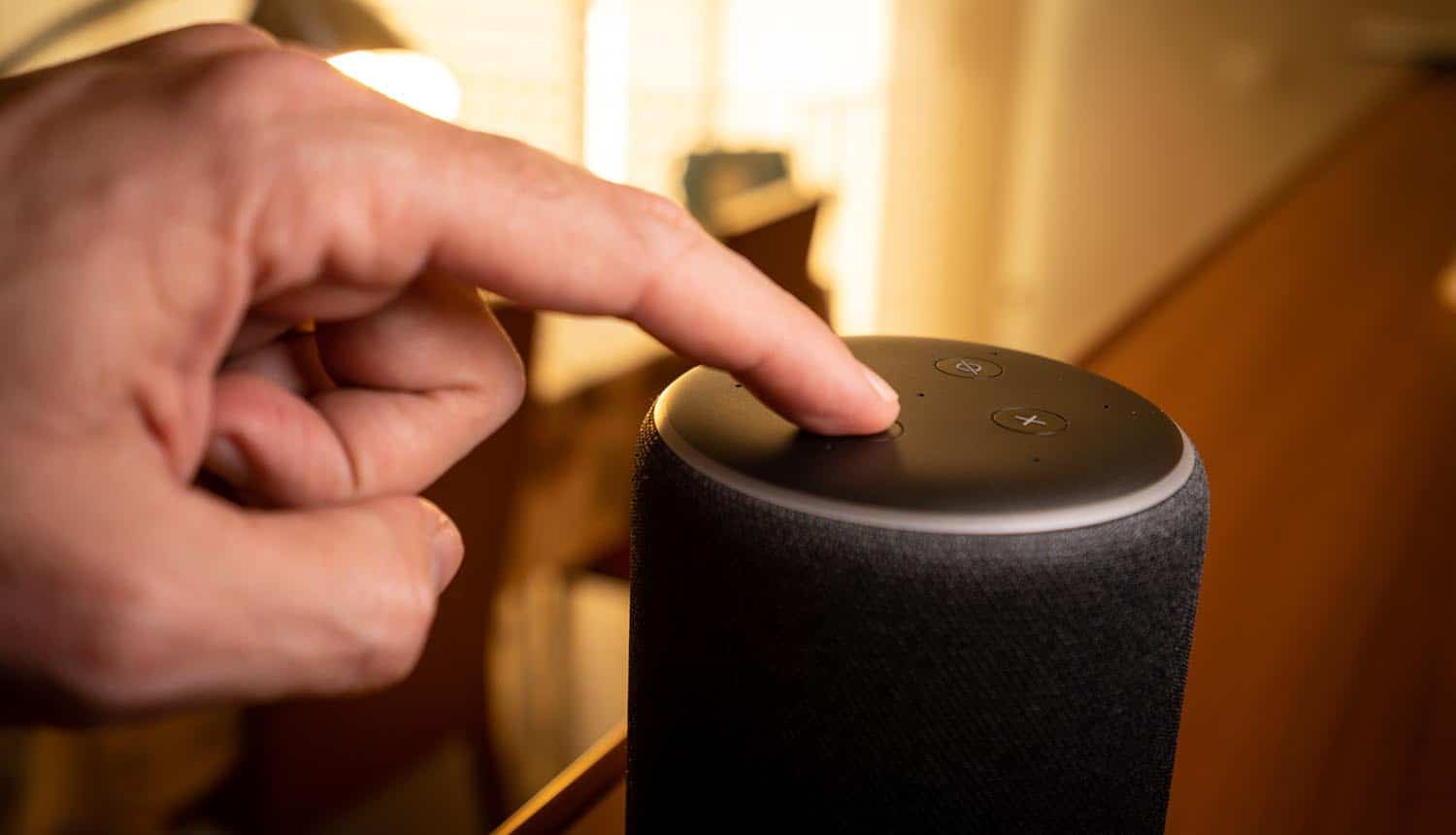Man touching smart speakers showing the concern from Americans on the amount of data collected from smart speakers