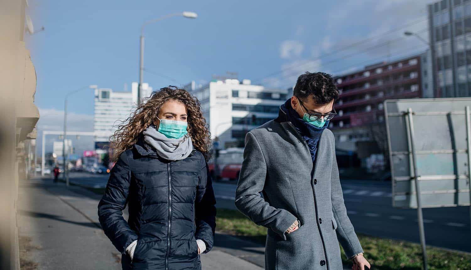 Man and woman wearing face masks on street showing the importance of ethical data privacy in time of COVID-19