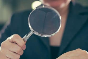 Woman using a magnifying glass showing the projected global cost of financial crime compliance reaching over $180 billion