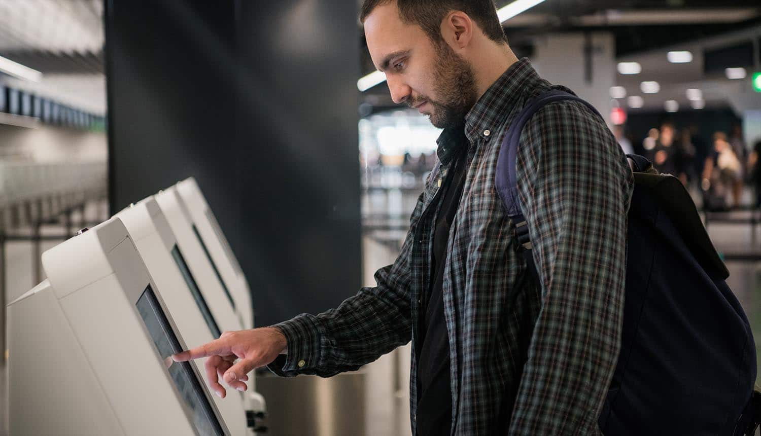 Man using check-in kiosk at airport showing how biometrics will transform airport travel
