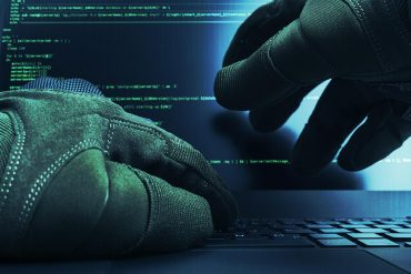 Hackers wearing gloves working on laptop showing what enterprises can do to battle cyber attack