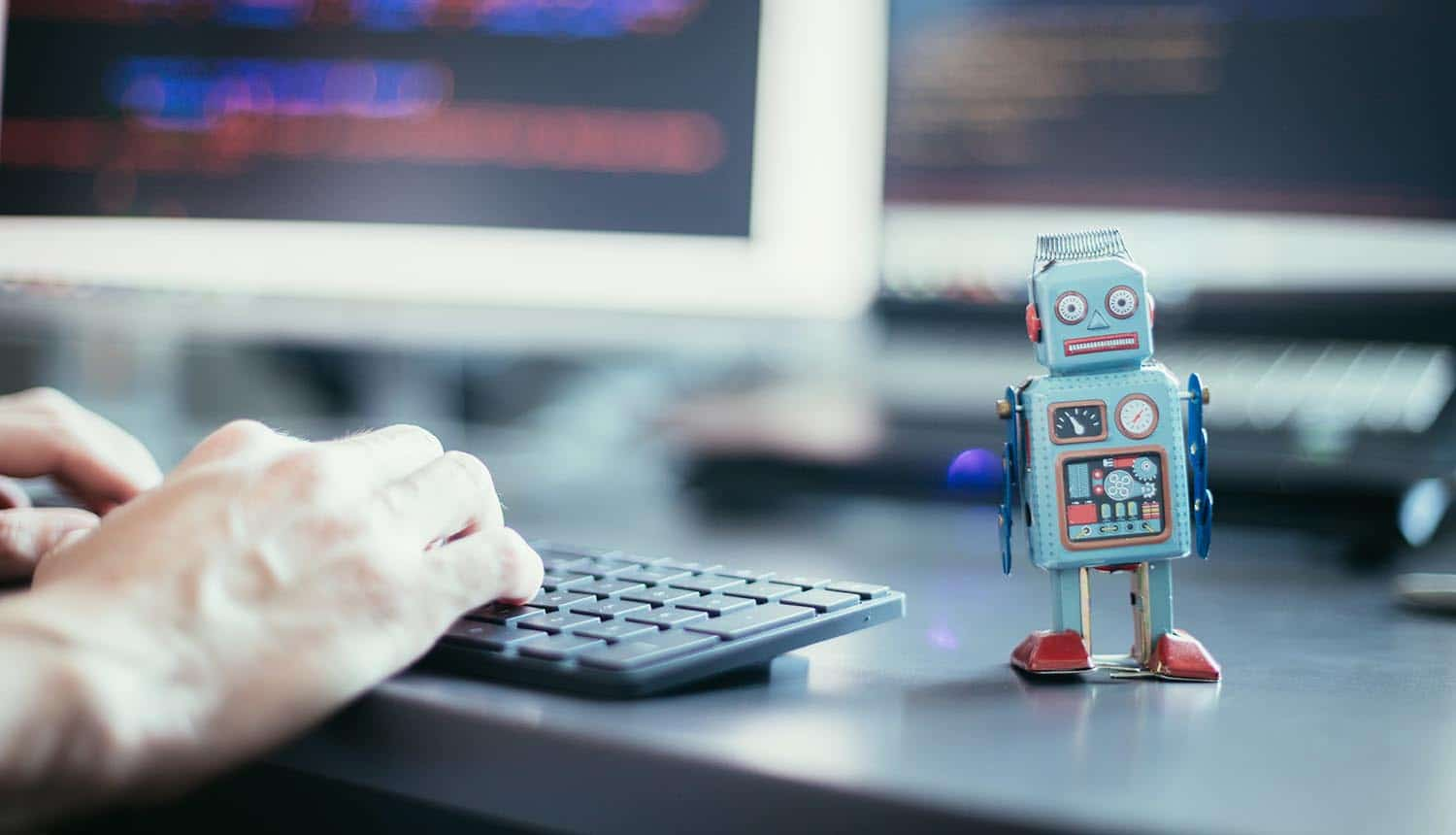 Man typing on keyboard next to a robot showing Russia's FSB building a massive IoT botnet capable of running nation-state DDoS attacks