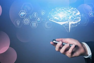 Hand of man in suit holding smartphone with glowing brain hologram showing new AI guidelines from FTC