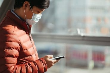 Man in mask using mobile showing the use of mobile phone location data to track coronavirus