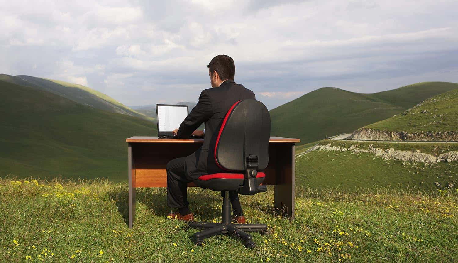 Man using laptop at desk in mountain field showing how you can minimize the cyber security risks of remote working