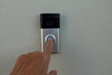 Man pressing a doorbell showing Amazon Ring assessing user demand for facial recognition feature in their products