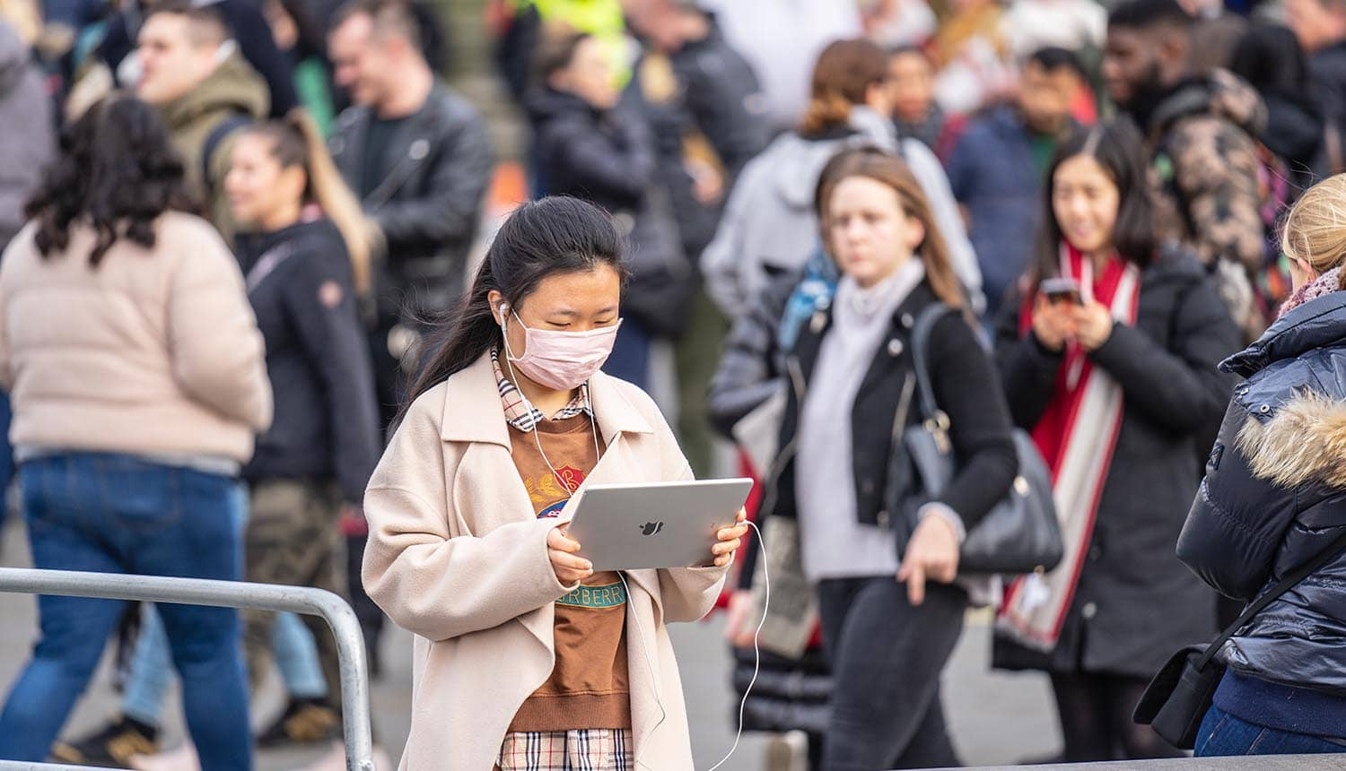 Woman in mask using tablet on street showing the debate over centralized or decentralized tracking for contact tracing app