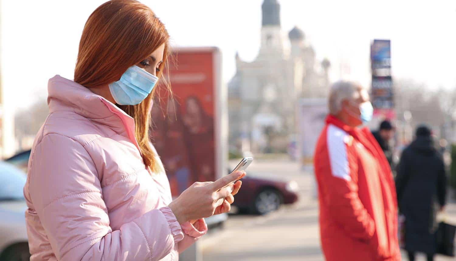 Woman in mask using mobile showing the unreported national security risk of COVID-19 contact tracing apps