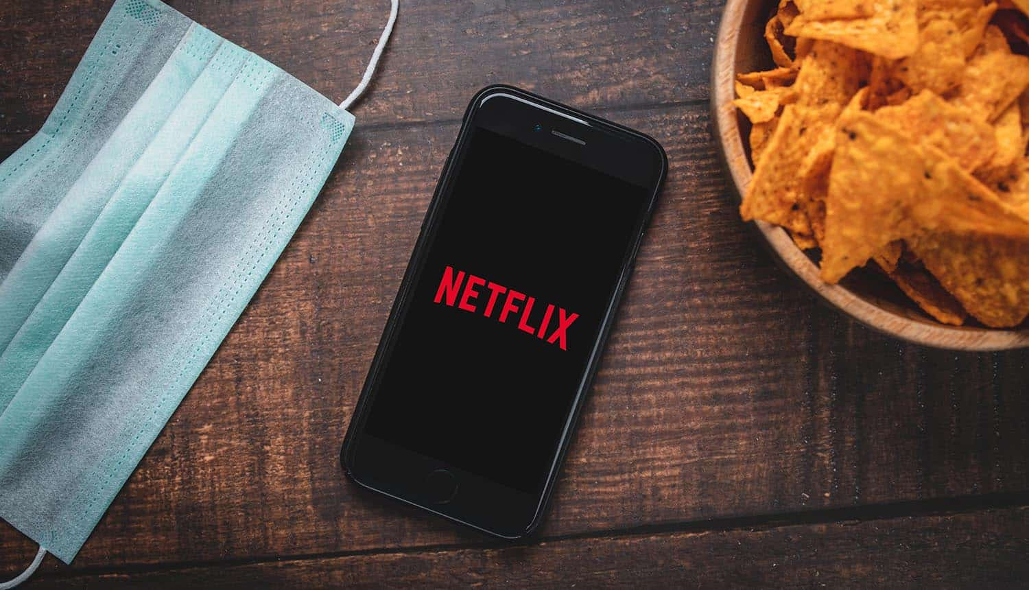 Phone with Netflix app logo and mask on table showing the increase in scam websites mimicking online streaming services