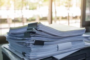 Stack of files on work desk in office showing data leak of legal documents from 190 law firms