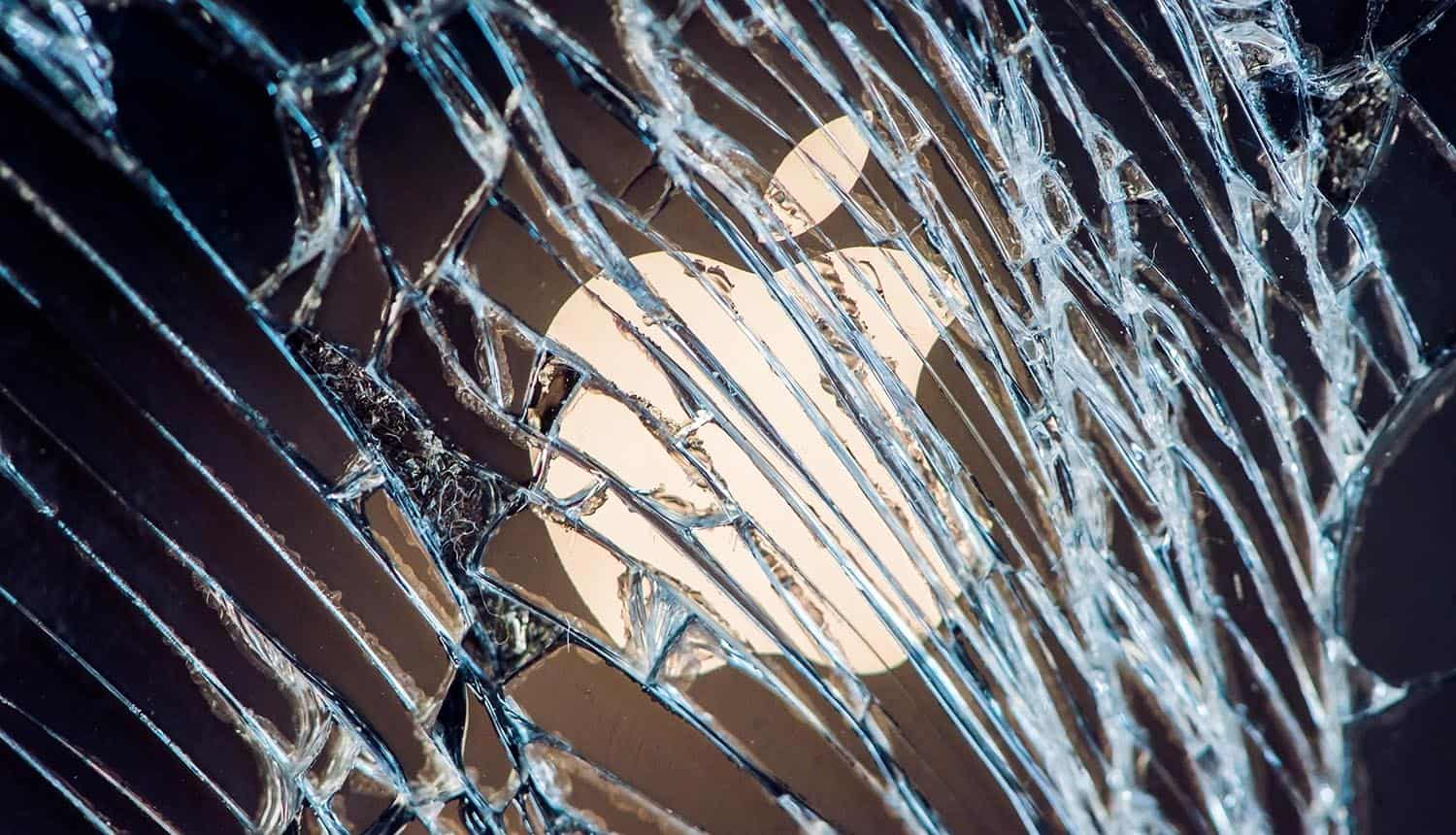 Apple company logo behind cracked screen showing the iPhone vulnerability that can be triggered by simply opening the default mail app