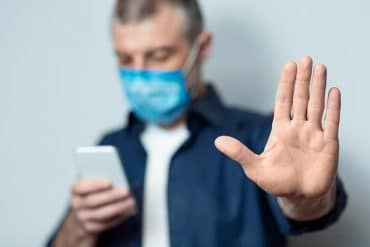 Man in mask using mobile showing how surveillance technology companies are selling spy tools as coronavirus contact tracers