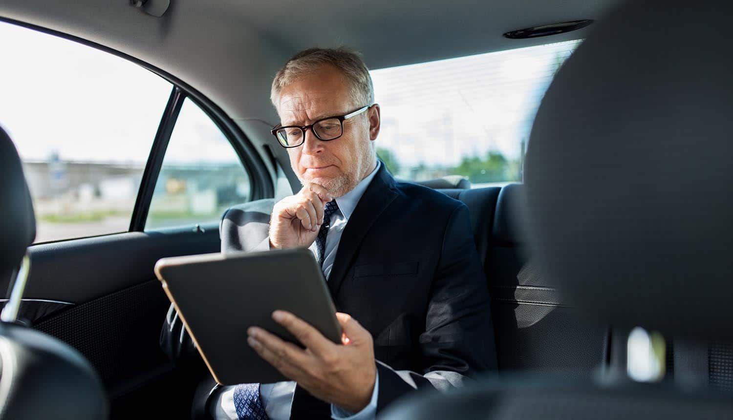 Businessman using tablet in car showing the Perswaysion phishing campaign that is targeting C-suite executives at international organizations