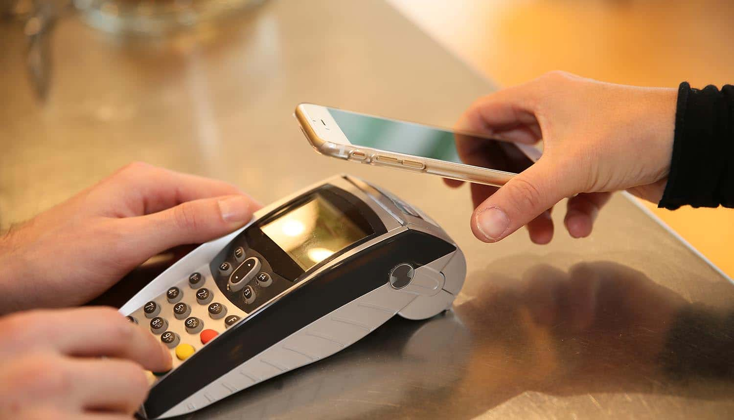 Payment transaction with mobile showing the three reasons to prioritize PCI compliance