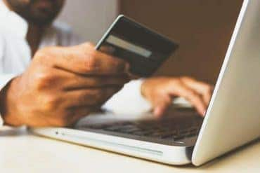 Man in front of laptop using credit card to make online transaction