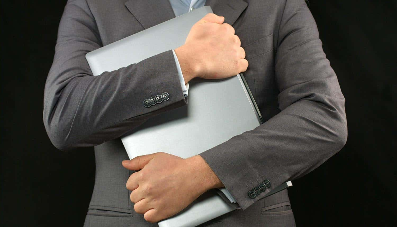 Man in business suit holding laptop computer tight showing data privacy concerns