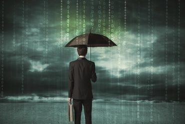 Businessman standing with umbrella showing cyber insurance becoming a necessity for companies