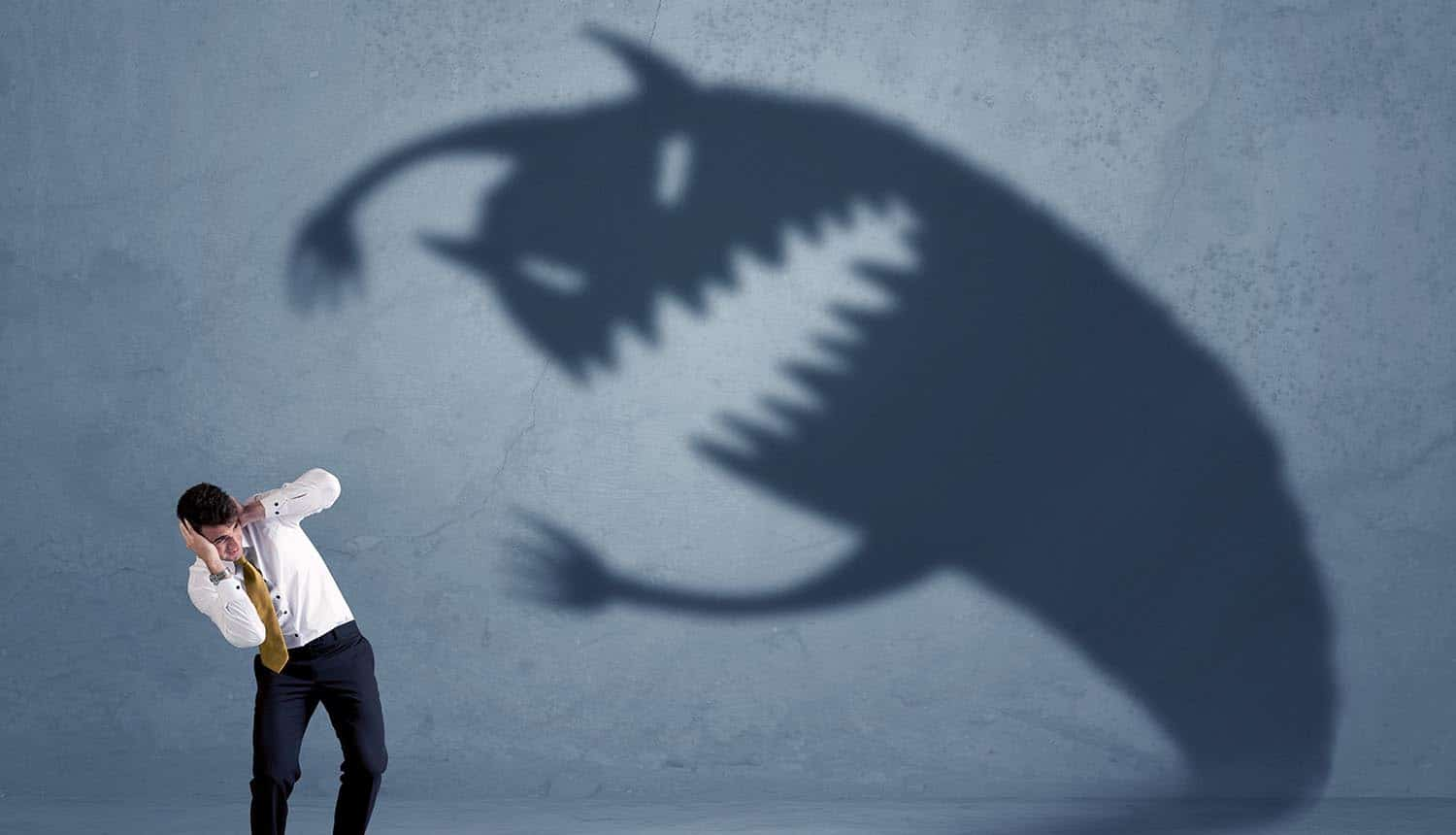 Man afraid of a monster shadow showing the methods to identify and avoid scareware scams