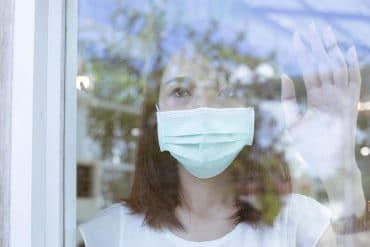 Woman in mask standing behind a window showing the new contact tracing wearable for COVID-19 tracking in Singapore