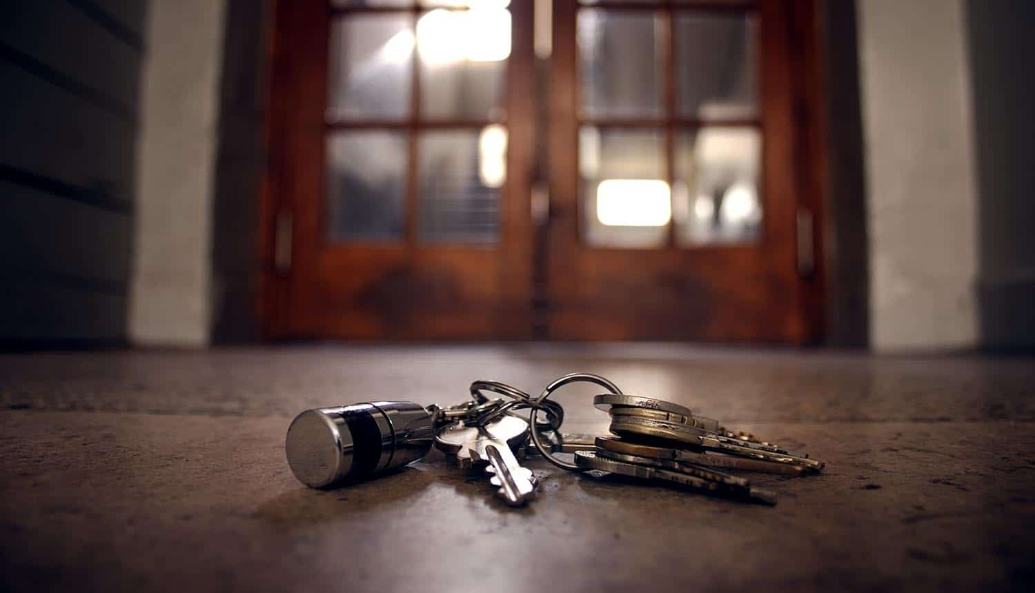 Keys on the floor in front of the door showing the benefits and risks of corporate security policies in employees' homes