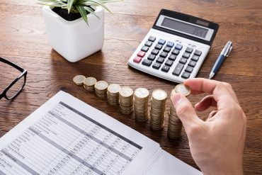 Man stacking coins with calculator on desk showing the increase in privacy compliance budget with evolving regulatory landscape