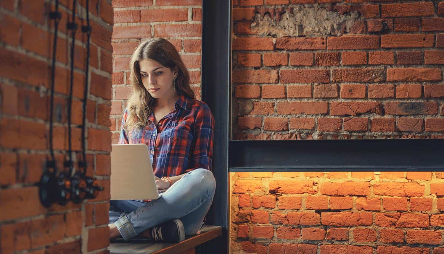 Woman with laptop in the loft showing the lack of safe data practices while remote working