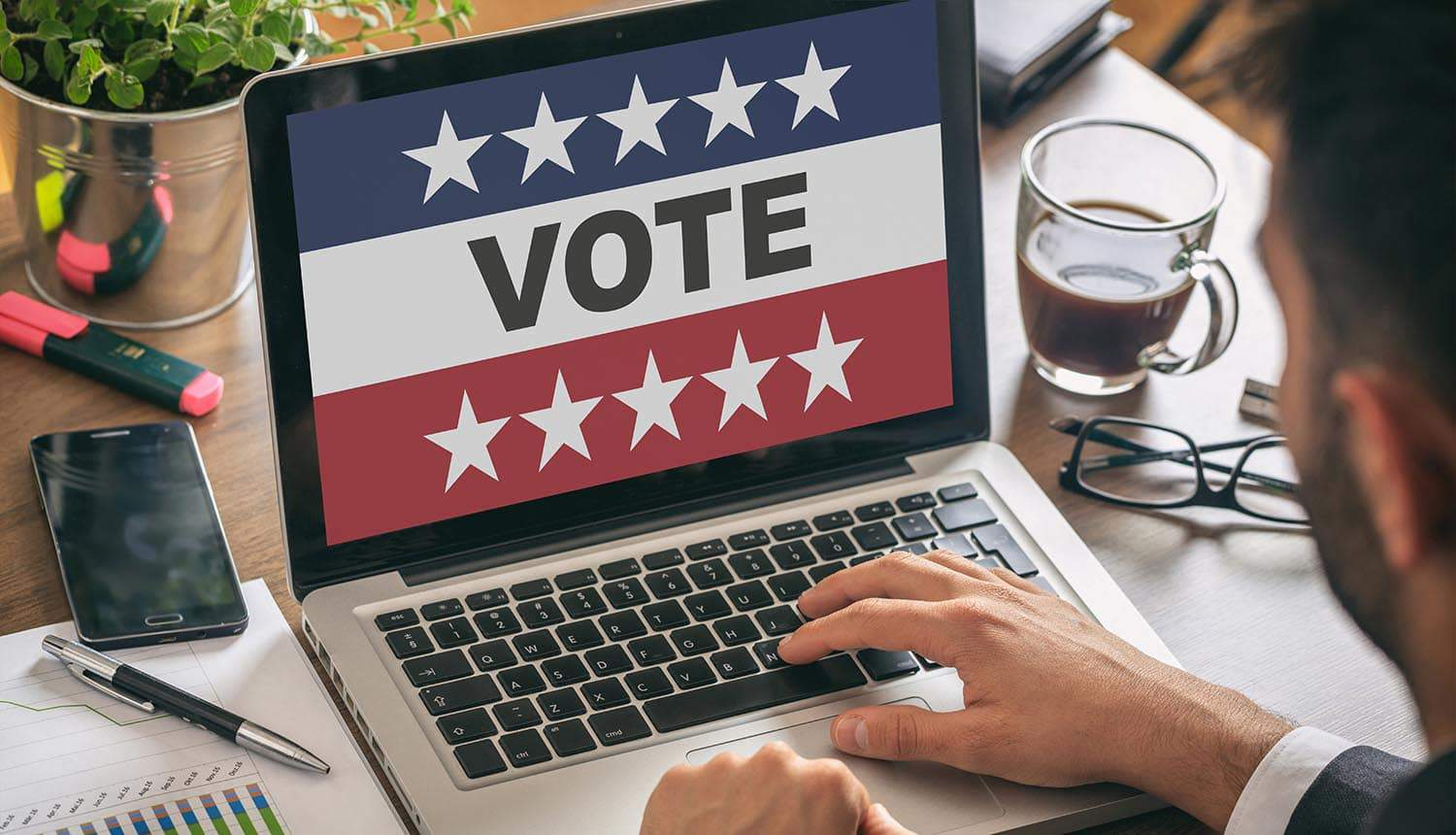 Man doing online voting on laptop showing the security flaws in U.S. online voting system that raised alarm over potential vote manipulation