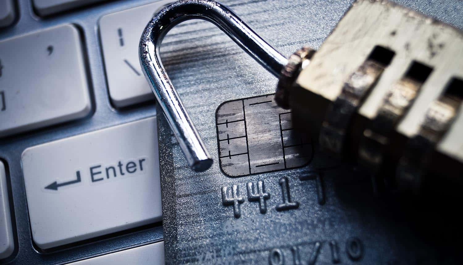 Broken padlock and credit card on keyboard showing replacement of 12 million bank cards due to internal security breach through master key at South African Postbank